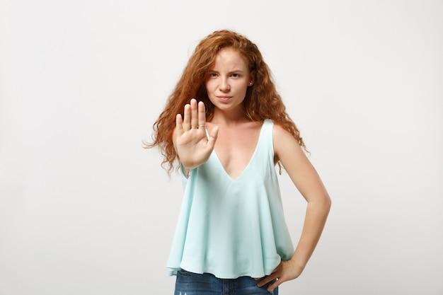 白い壁の背景、スタジオの肖像画に分離されたポーズでカジュアルな明るい服を着た若い深刻な赤毛の女性の女の子。人々のライフスタイルの概念。コピースペースをモックアップします。手のひらで停止ジェスチャーを表示しています。
