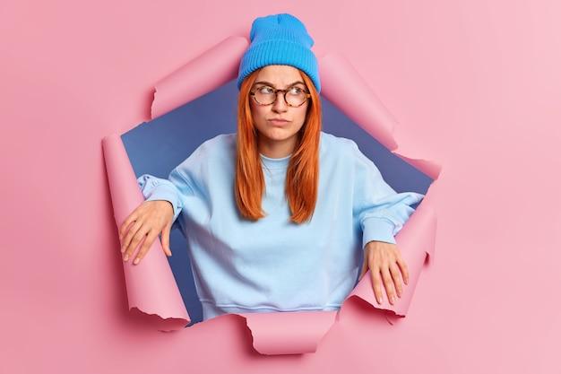 Giovane donna seria scettica rossa guarda pensierosamente da parte ha un'espressione pensierosa pensa a qualcosa di non molto piacevole indossa cappello e maglione sfonda la carta
