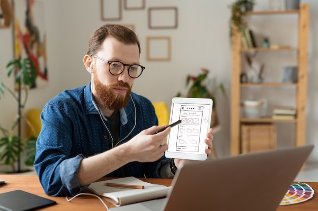 Young serious software developer pointing at sketch of smartphone model on tablet display while consulting with colleague in front of laptop