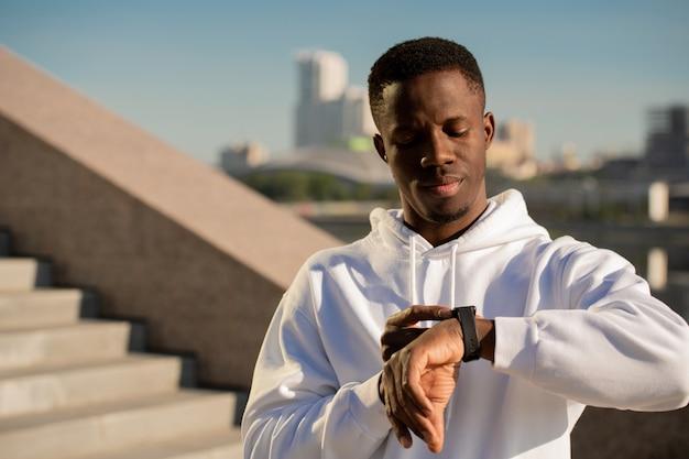 都市環境で朝ジョギングしながら左手首のスマートウォッチを見ているアフリカ民族の若い真面目なスポーツマン