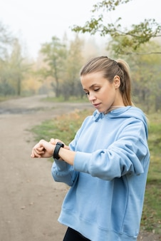 Young serious sportswoman in blue hoodie looking at wristwatch before training while standing in front of camera against forest path