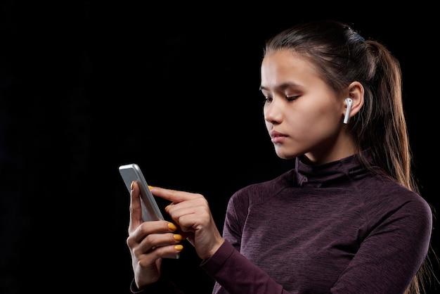 スマートフォンのタッチスクリーンを指しているコードレスイヤホンを持つ若い真面目なスポーツウーマン