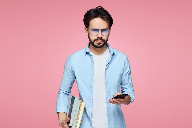 本と携帯電話を持っている若い真面目な学生