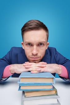 Young serious student keeping chin over hands by stack of books while sitting by desk