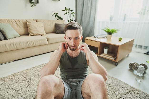Молодой серьезный потный спортсмен делает приседания и смотрит на вас, сидя на ковре в домашней обстановке