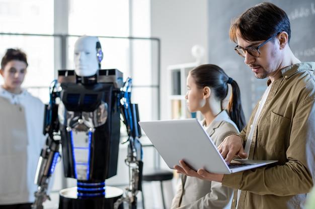 Молодой серьезный учитель с ноутбуком просматривает онлайн-материалы, в то время как его ученики делают презентацию способностей роботов на семинаре