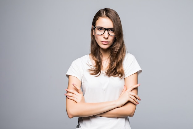 白いtシャツとブルージーンズのメガネの若い深刻な思考の女性は白いスタジオの背景の前に滞在します。