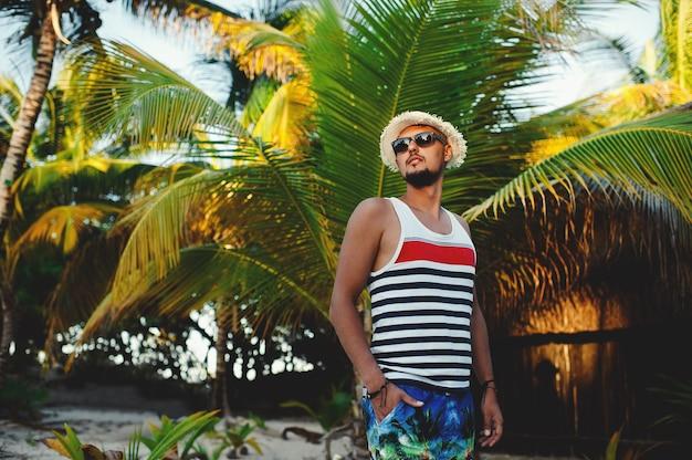Молодой серьезный туристический мужчина позирует на фоне пальм