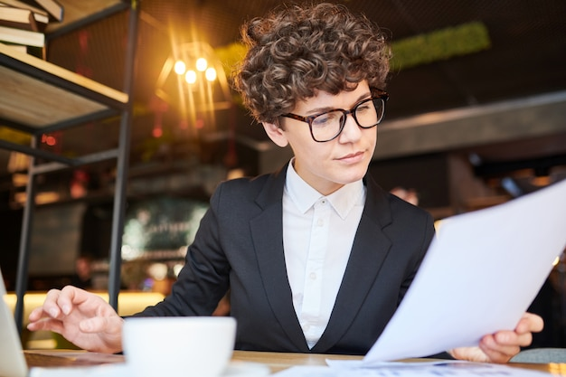 Young serious trader reading financial paper while analyzing information and comparing numbers