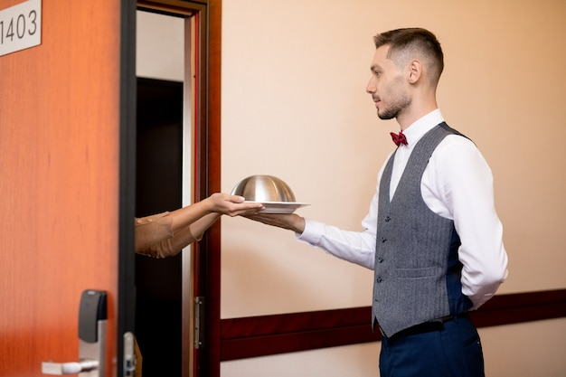 ドアを開けて立っている間ホテルのゲストの1人に食べ物とクロッシュを渡す若い深刻なウェイター