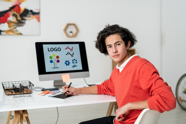 Молодой серьезный веб-дизайнер со стилусом и графическим планшетом сидит за столом перед камерой в домашней обстановке