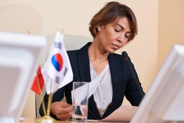 コンファレンスホールに座っている間書類に目を通すことに集中している若い深刻な身なりのよい女性実業家