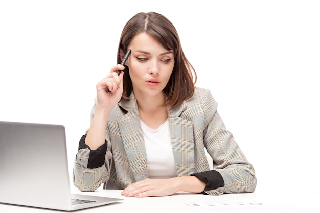 Young serious white collar worker reading paper or looking for new ideas while sitting by desk