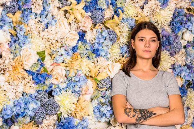 Young serious woman between different flowers