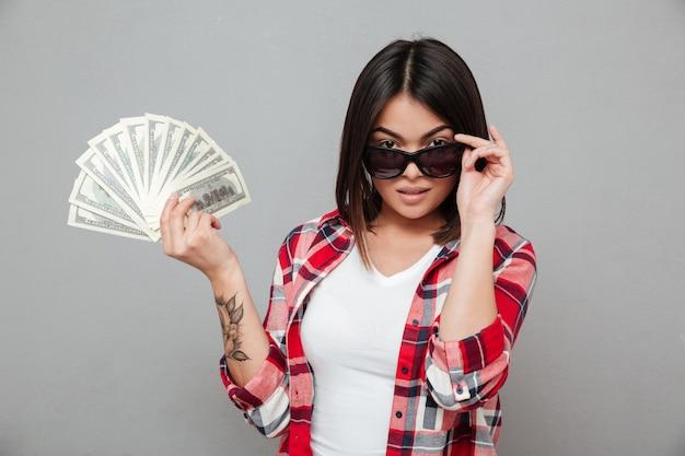 Молодая серьезная женщина держит деньги за серую стену