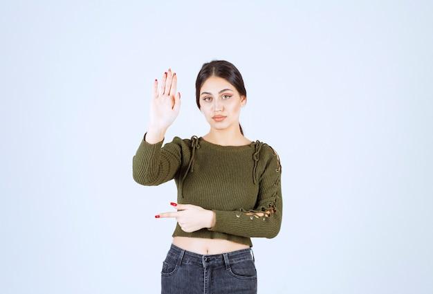 정지 신호를 표시 하 고 멀리 가리키는 젊은 심각한 여자 모델.