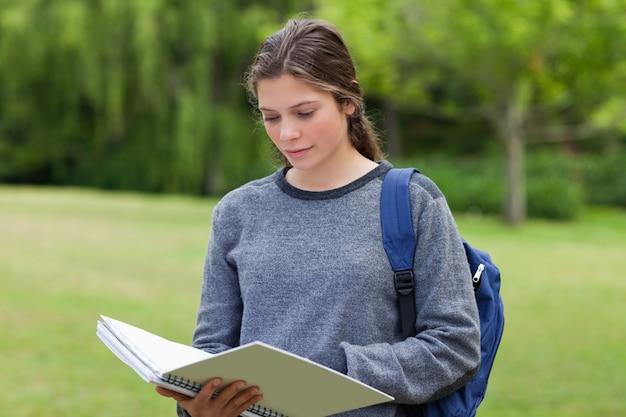 公園に立っている間に彼女のノートを読んでいる若い深刻な女性