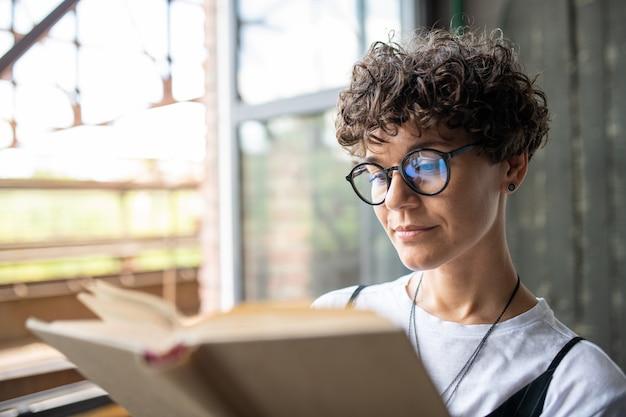 自宅で余暇を過ごしながら小説のページを見て茶色の巻き毛を持つ深刻な女性