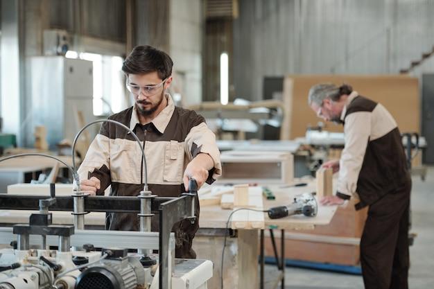 Молодой серьезный работник мебельной фабрики смотрит на вас, стоя у верстака на стене интерьера мастерской во время работы