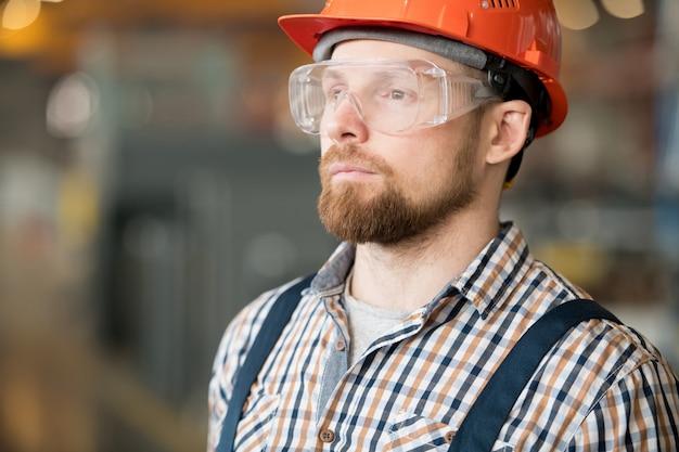 作業プロセスを制御しながらまっすぐ見て産業プラントの若い深刻な労働者