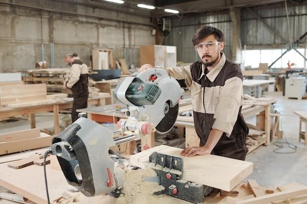 Молодой серьезный рабочий или инженер мебельной фабрики в униформе и очках, стоящий перед камерой в большой мастерской
