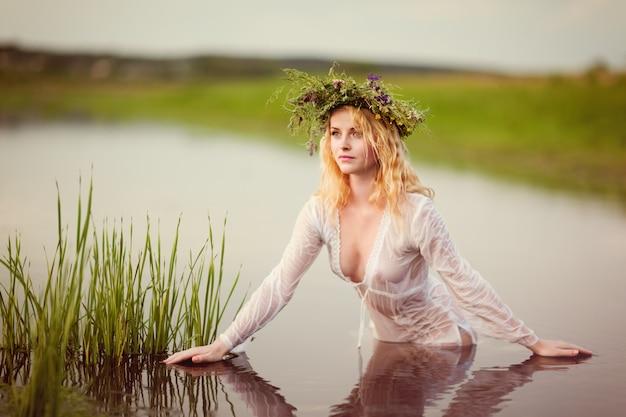 Молодая сексуальная красивая блондинка женщина в белом мини-платье и цветочном венке стоит и пробует воду