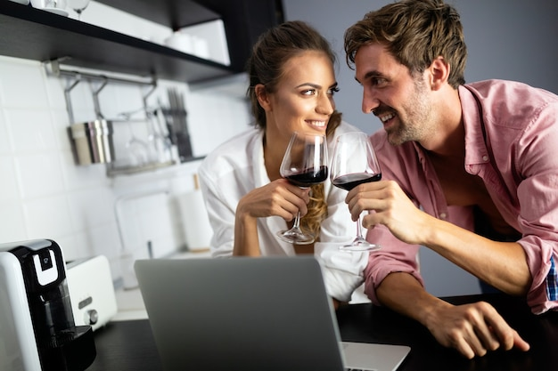 Young sexy beautiful couple cooking together and drinking wine