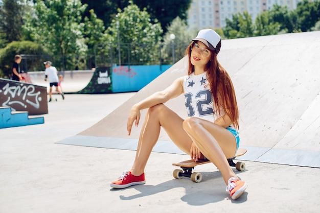 젊은 섹시 아름다운 날씬한 여자는 도시에서 스케이트 보드에 앉아있다. 모자와 선글라스에 유행 소녀 소식통.
