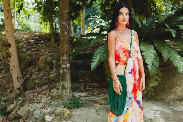 Giovane bella donna sexy in abito colorato, stile hippie estivo, vacanza tropicale, gambe abbronzate, sandali, borsa verde con frangia, accessori, sorridente, felice