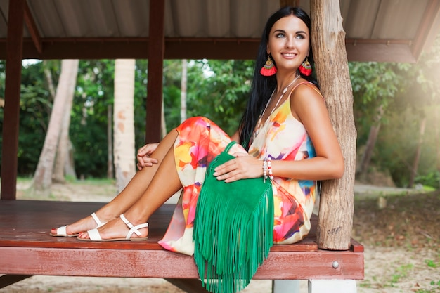 Young sexy beautiful woman in colorful dress, summer hippie style, tropical vacation, tanned legs, sandals, green handbag with fringe, accessories, smiling, happy