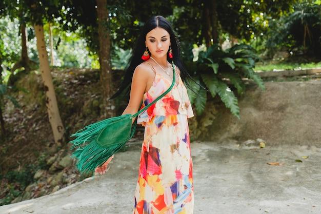 カラフルなドレス、夏のヒッピースタイル、熱帯の休暇、日焼けした足、サンダル、フリンジ付きの緑のハンドバッグ、アクセサリー、笑顔、幸せの若いセクシーな美しい女性