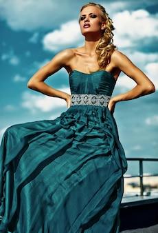 青い空でポーズのイブニングドレスの若いセクシーな金髪の女性モデル