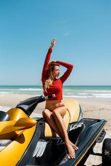 日差しの中でビーチで水スクーターに座っている赤い服を着た完璧なボディを持つ若いセクシーなブロンドの女性。夏の週末または休暇。エクストリームスポーツ。