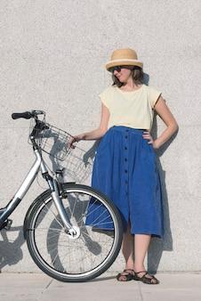 若いセクシーなブロンドの女の子が青いスカートと帽子で自転車の近くに立っています