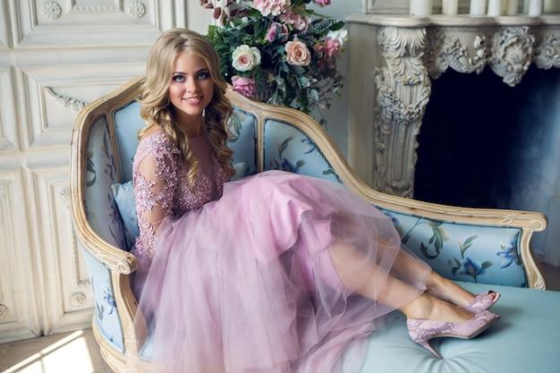 レースのピンクのドレスでソファに座っている若いセクシーなブロンドの女の子は彼女の頭を回し、肖像画を笑顔