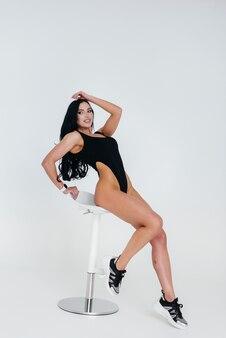 흰색 바탕에 검은색 바디 수트에 젊은 섹시 한 갈색 머리. 완벽한 운동선수.