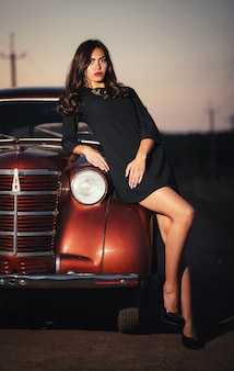 Молодая сексуальная брюнетка с длинными ногами в черном платье и туфлях на высоких каблуках лежит на капоте бордового ретро-автомобиля на проселочной дороге поздним вечером