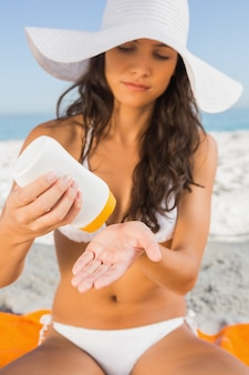 Young sexy brunette with straw hat putting on sun cream