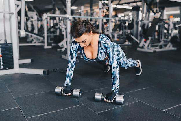 젊은 섹시 갈색 머리 체육관에서 손으로 무게와 함께 작동합니다. 선수 빌더 근육 라이프 스타일.
