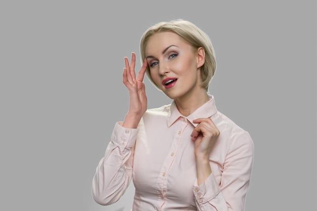 灰色の背景に若いセクシーなビジネス女性。オフィスシャツの魅惑的なビジネスレディの肖像画。セクシュアリティと誘惑。