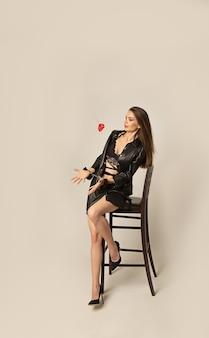 젊은 섹시 한 백인 갈색 머리 여자 속옷에 앉아있는 동안 그녀의 손에 붉은 마음으로 의자와 수갑. bdsm 섹스 복종과 지배의 개념