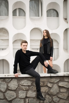 Young sexy couple in black clothes posing with a background on the white wall