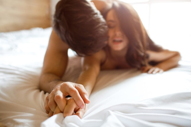 Young sexy couple have intimacy on bed. man on top. holding her ahnd in his. seduction and temptation. lust and passion. sensual woman screaming. enjoy process.