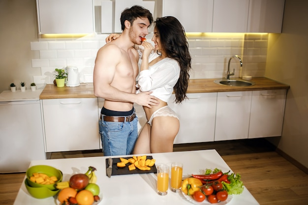Young sexy couple have intimacy in kitchen in night. beautiful hot woman embrace and kiss shirtless guy. model wear white shirt and lingerie. fruit and vegetables on table.