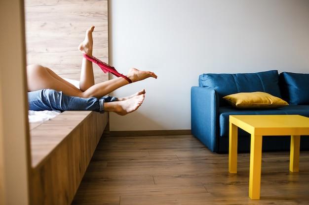 Молодая сексуальная пара интимно на кровати. вырезать вид женского нижнего белья между ног, позируя на камеру. модель, лежащая на человеке