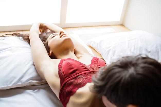 Молодая сексуальная пара интимно на кровати. изображение страстной женщины, наслаждающейся и держащей руки вверх. парень целует ее живот. интимный момент. чувствительный процесс. все вместе
