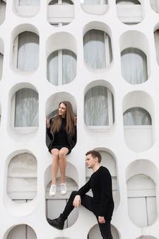 흰 벽에 배경으로 포즈를 취하는 검은 옷을 입은 젊은 섹시한 커플