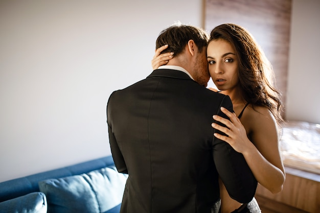 거실에서 젊은 섹시 한 커플. 검은 란제리에 아름 다운 매력적인 젊은 여자 남자를 포용 하 고 카메라를 봐. 열정으로 사업가 터치 모델.