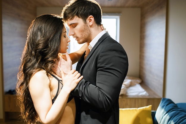 Young sexy couple in living room. businessman in suit touch woman in lingerie. passionate moment. lust, seduction and sensuality. bdsm, standing pose