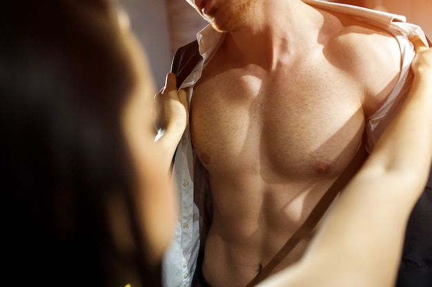 Young sexy couple in living room. cut view of well-built and slim man's body and chest. woman put off his shirt and jacket. seductive and sensual moment.